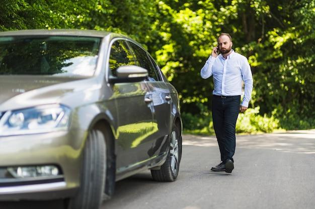 Mann, der nahe dem auto spricht auf mobiltelefon geht Kostenlose Fotos