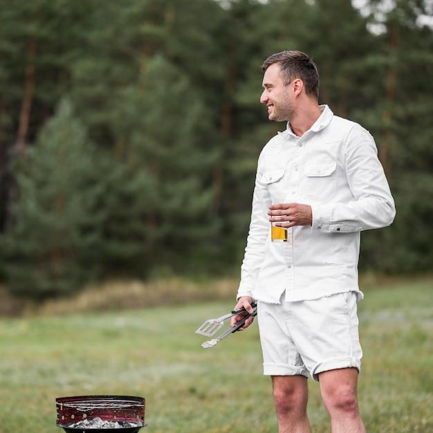 Mann, der neben dem grillen sitzt und ein bier hat Kostenlose Fotos