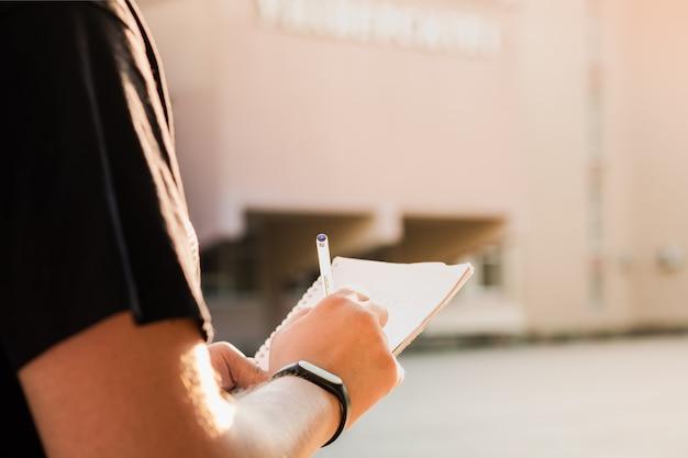 Mann, der notizen außerhalb einer bildungseinrichtung macht. die hände der jungen männlichen person, die einen notizblock und einen stift halten und informationen draußen schreiben Premium Fotos