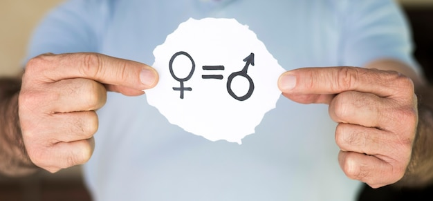 Mann, der papier mit geschlechtssymbolen hält Premium Fotos