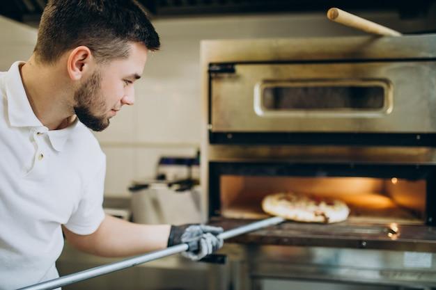 Mann, der pizza in ofen bei pizzeria setzt Kostenlose Fotos