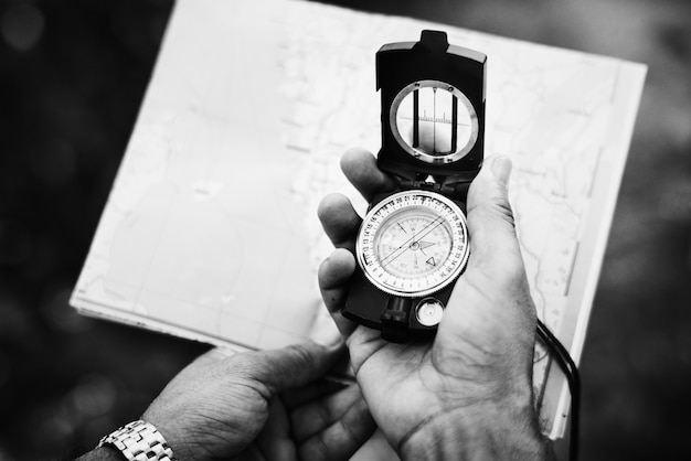 Mann, der richtung auf einen kompass überprüft Kostenlose Fotos