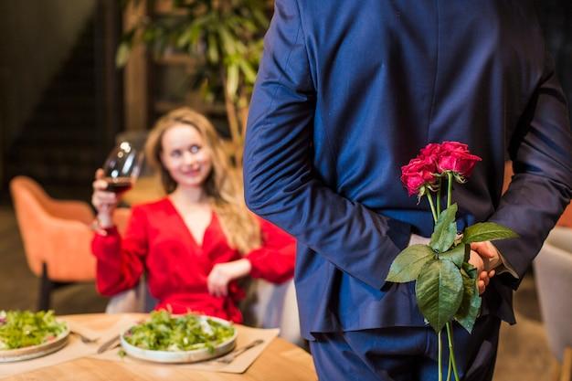 Mann, der rosenblumenstrauß hinten hält Kostenlose Fotos