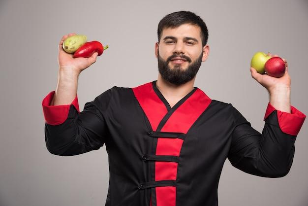 Mann, der roten pfeffer, äpfel und zucchini hält. Kostenlose Fotos
