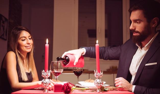 Mann, der rotwein in ein glas frau gießt Kostenlose Fotos