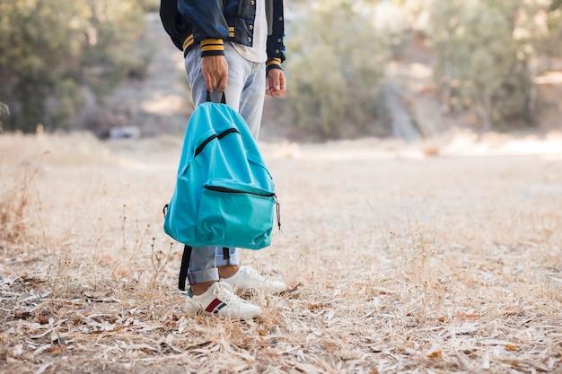 Mann, der rucksack im park hält Kostenlose Fotos