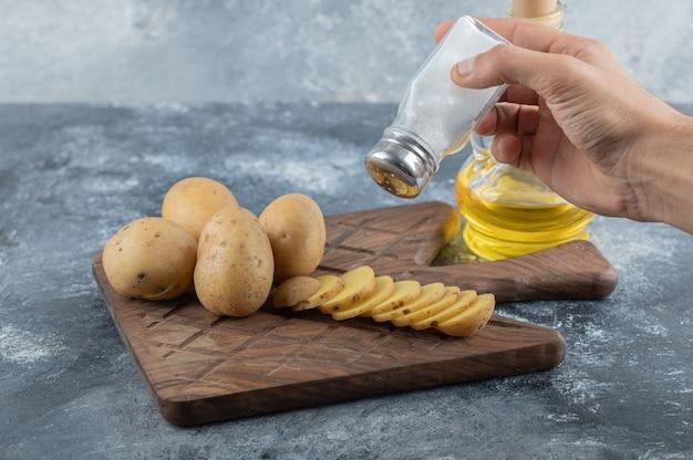 Mann, der salz auf geschnittene kartoffeln gießt. hochwertiges foto Kostenlose Fotos