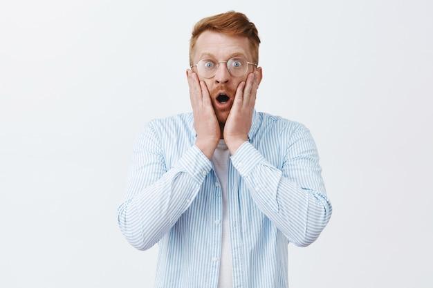 Mann, der schockiert ist, schreckliche szene zu sehen. porträt eines betäubten verängstigten rothaarigen mannes in brille und hemden, der den kiefer fallen lässt, vor erstaunen nach luft schnappt und besorgt über die graue wand starrt Kostenlose Fotos