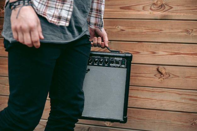 Mann, der schwarzen elektrischen gitarrenverstärker für musiker hält Premium Fotos