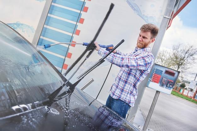 Mann, der sein auto in einer selbstbedienung putzt Kostenlose Fotos