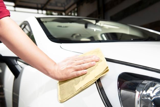 Mann, der sein auto mit mikrofasertuch säubert Premium Fotos