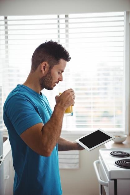 Mann, der sein digitales tablett beim glas saft verwendet Kostenlose Fotos