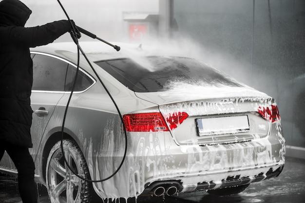 Mann, der sein graues auto unter hochdruckwasser im freien wäscht. - rückansicht Premium Fotos