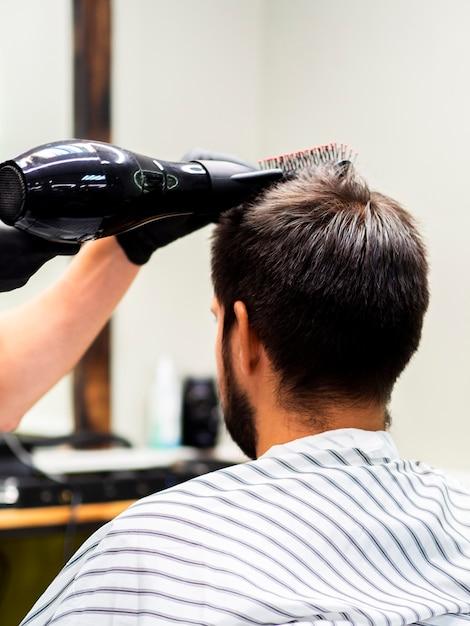 Mann, der sein haar mit einem trockner getrocknet erhält Kostenlose Fotos