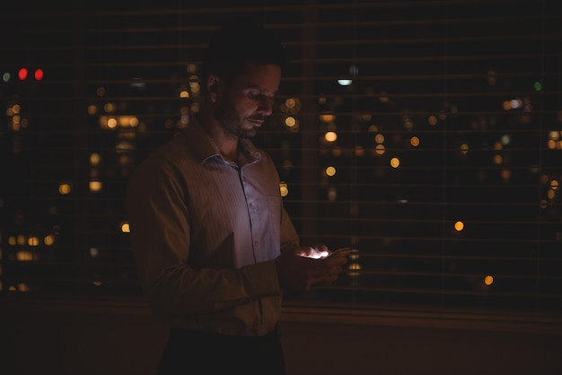 Mann, der sein handy in der nähe von jalousien benutzt Kostenlose Fotos