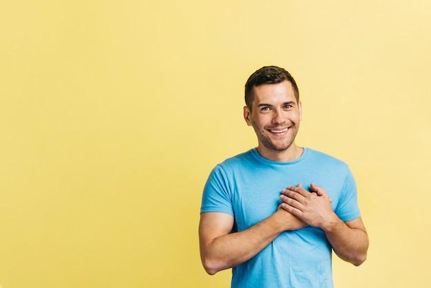 Mann, der seine hände an seinem herzen hält Kostenlose Fotos