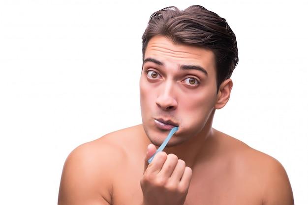 Mann, der seine zähne getrennt auf weiß putzt Premium Fotos