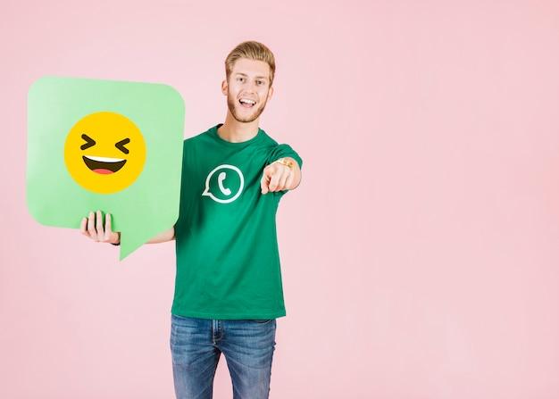 Mann, der seinen finger beim halten der spracheblase mit lächelndem emoji zeigt Kostenlose Fotos
