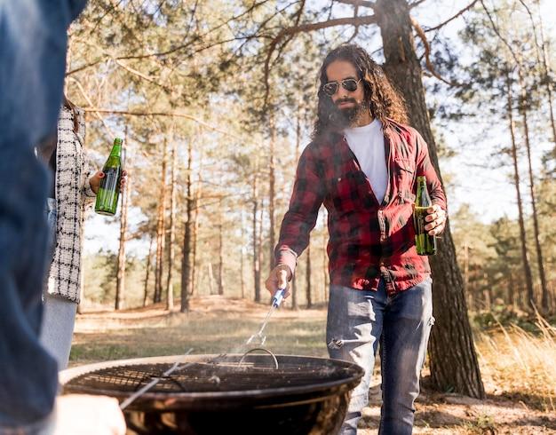 Mann, der sich um das grillen kümmert, während er ein bier hat Kostenlose Fotos