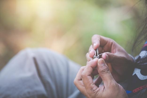 Mann, der sitzt, um nägel zu schneiden. Kostenlose Fotos