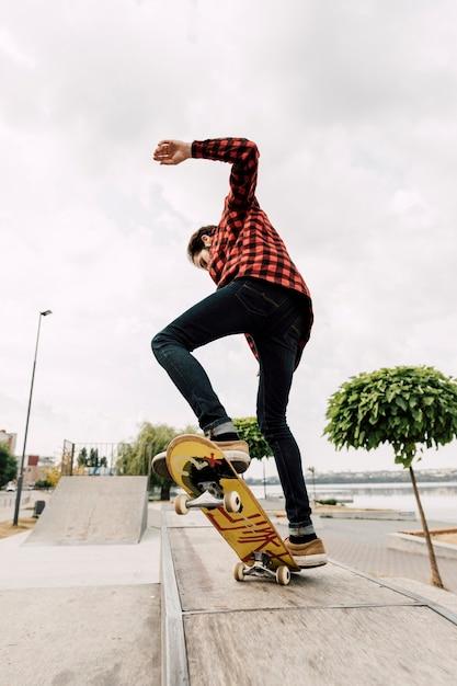 Mann, der skateboardtricks im park tut Kostenlose Fotos