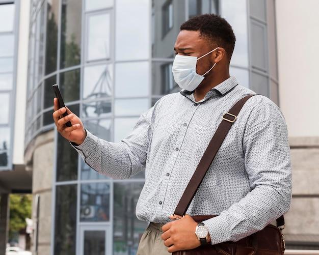 Mann, der smartphone auf seinem weg zur arbeit beim tragen der maske betrachtet Kostenlose Fotos