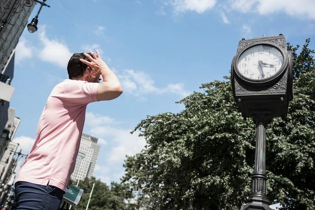 Mann, der straßenuhr betrachtet Kostenlose Fotos