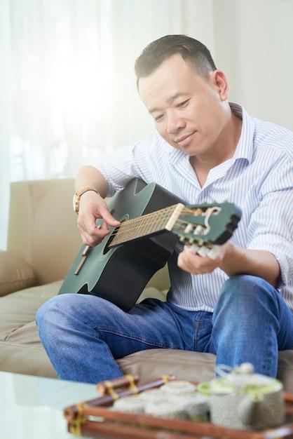 Mann, der studiert, um gitarre zu spielen Kostenlose Fotos