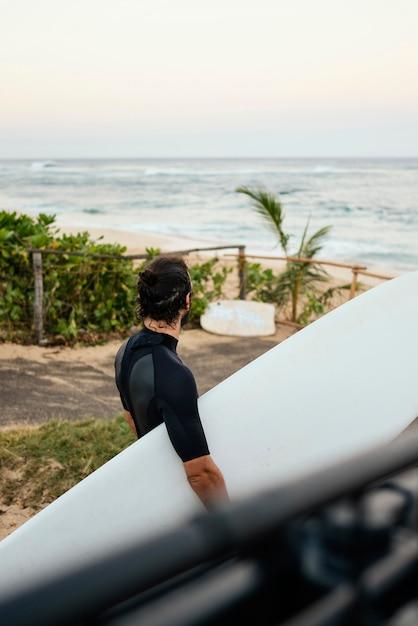 Mann, der surferkleidung trägt und sein surfbrett hält Kostenlose Fotos