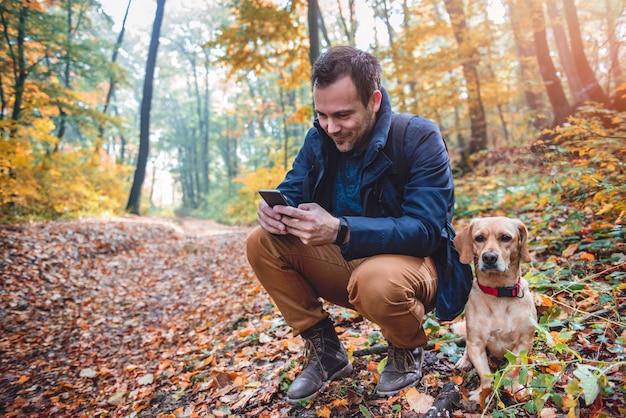 Mann, der telefon im bunten herbstwald verwendet Premium Fotos