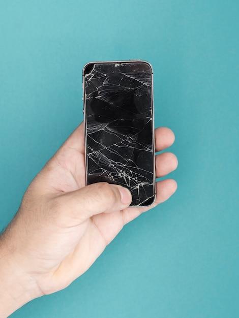Mann, der telefon mit zerbrochenem schirm hält Kostenlose Fotos