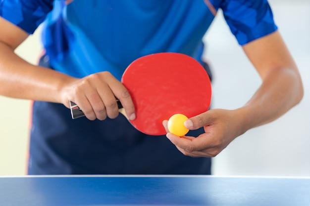 Mann, der tischtennis mit schläger und ball in einer sporthalle spielt Premium Fotos