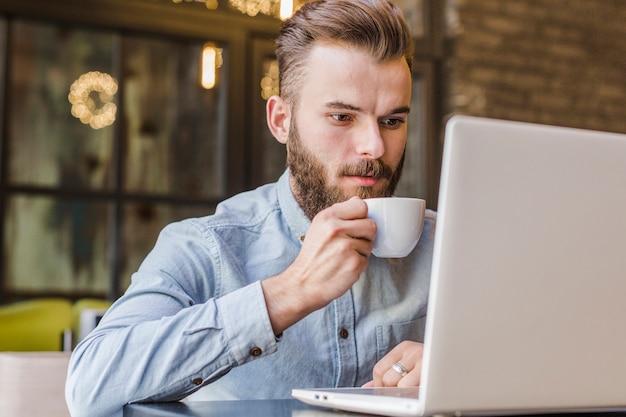 Mann, der trinkenden tasse kaffee des laptops verwendet Kostenlose Fotos