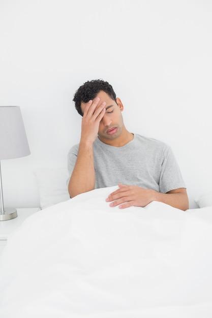 Mann, der unter kopfschmerzen im bett leidet Premium Fotos