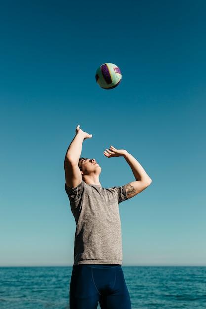 Mann, der volleyball am strand spielt Kostenlose Fotos