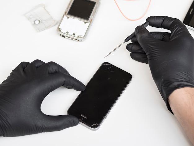 Mann, der wartungsarbeiten an einem telefon erledigt Kostenlose Fotos