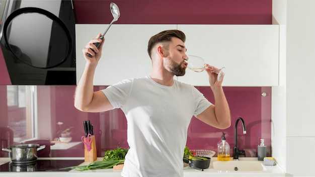 Mann, der wein trinkt und im mittleren schuss der küche herumalbert Kostenlose Fotos