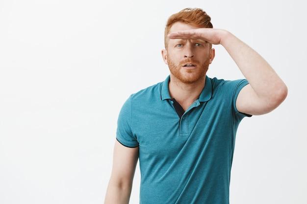 Mann, der weit weg schaut, blinzelt und handfläche auf stirn hält, um augen vor sonnenlicht zu bedecken und klar zu sehen, konzentriert und interessiert zu stehen, poloshirt über graue wand zu grüßen Kostenlose Fotos