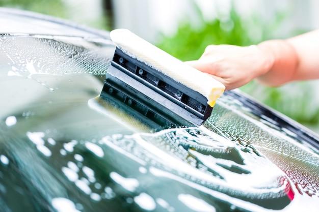 Mann, der windschutzscheibe während der autowäsche säubert Premium Fotos