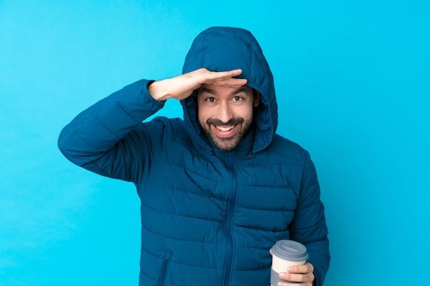 Mann, der winterjacke trägt und einen kaffee zum mitnehmen über isoliertem blau hält, das weit weg mit der hand schaut, um etwas zu schauen Premium Fotos