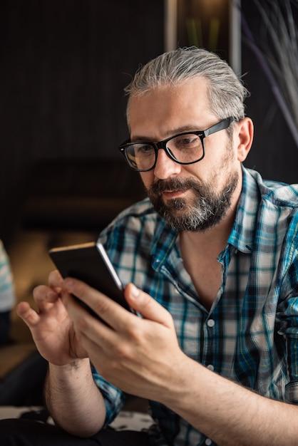 Mann, der zu hause intelligentes telefon verwendet Premium Fotos