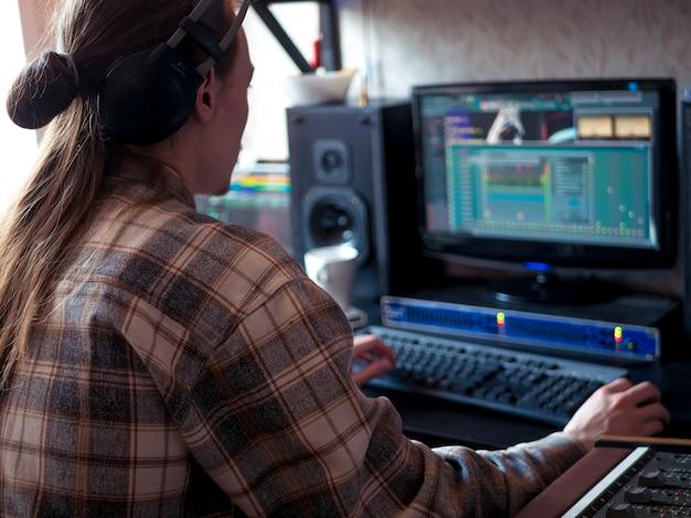 Mann, der zu hause studio mit berufsmusikausrüstung sitzt Premium Fotos