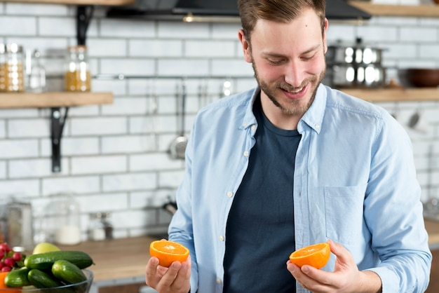 Mann, der zwei orange scheiben in der küche betrachtet Kostenlose Fotos