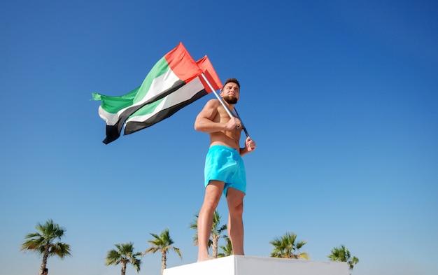 Mann, der zwei uae-flaggen hält Premium Fotos