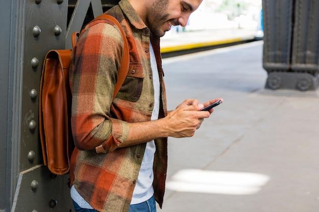 Mann des hohen winkels an der u-bahn unter verwendung des telefons Kostenlose Fotos