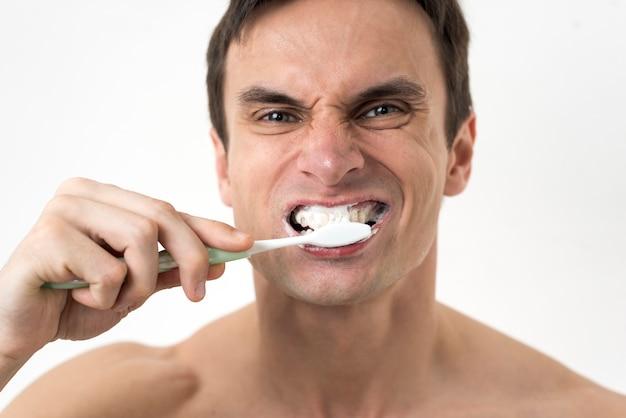 Mann, die zähne putzen hautnah Kostenlose Fotos