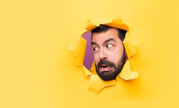 Mann durch ein lochpapier, das seitlich schaut Premium Fotos