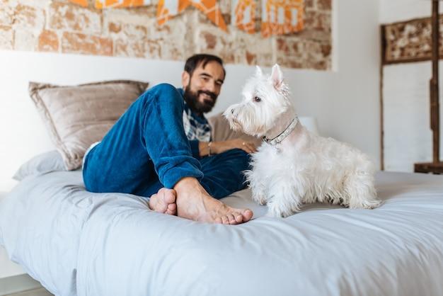 Mann entspannt zu hause sitzen im bett mit seinem hund Premium Fotos
