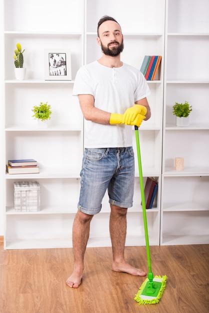 Mann erledigt etwas reinigungsarbeit zu hause. Premium Fotos