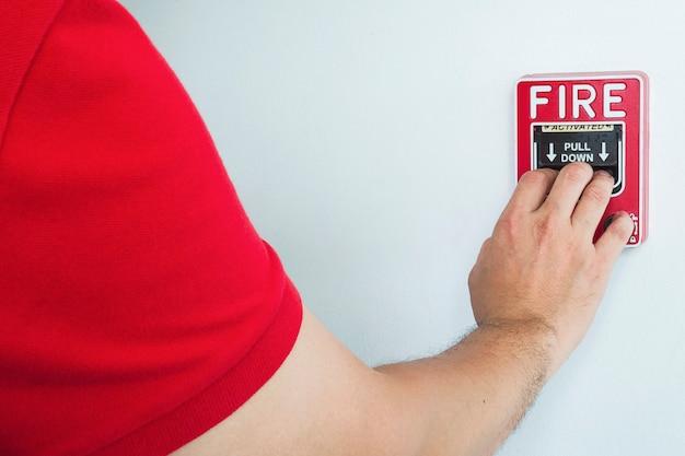 Mann erreicht seine hand, um feuermelder-handstation zu drücken Kostenlose Fotos